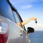 Costa Rica car rental woman holding key overlooking ocean