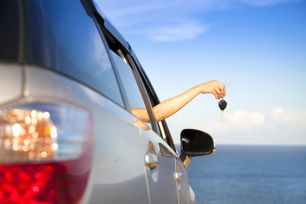 Costa Rica car rental woman holding key overlooking ocean
