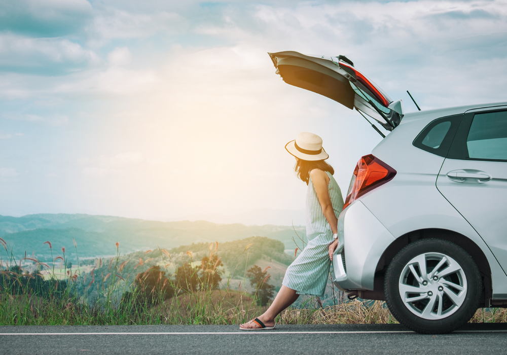 woman sitting on hatchback of rental car in Costa Rica