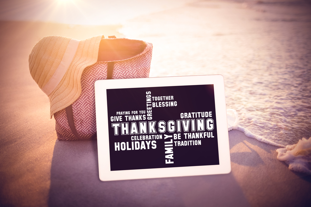 Thanksgiving words against bag with sunhat and flip flop